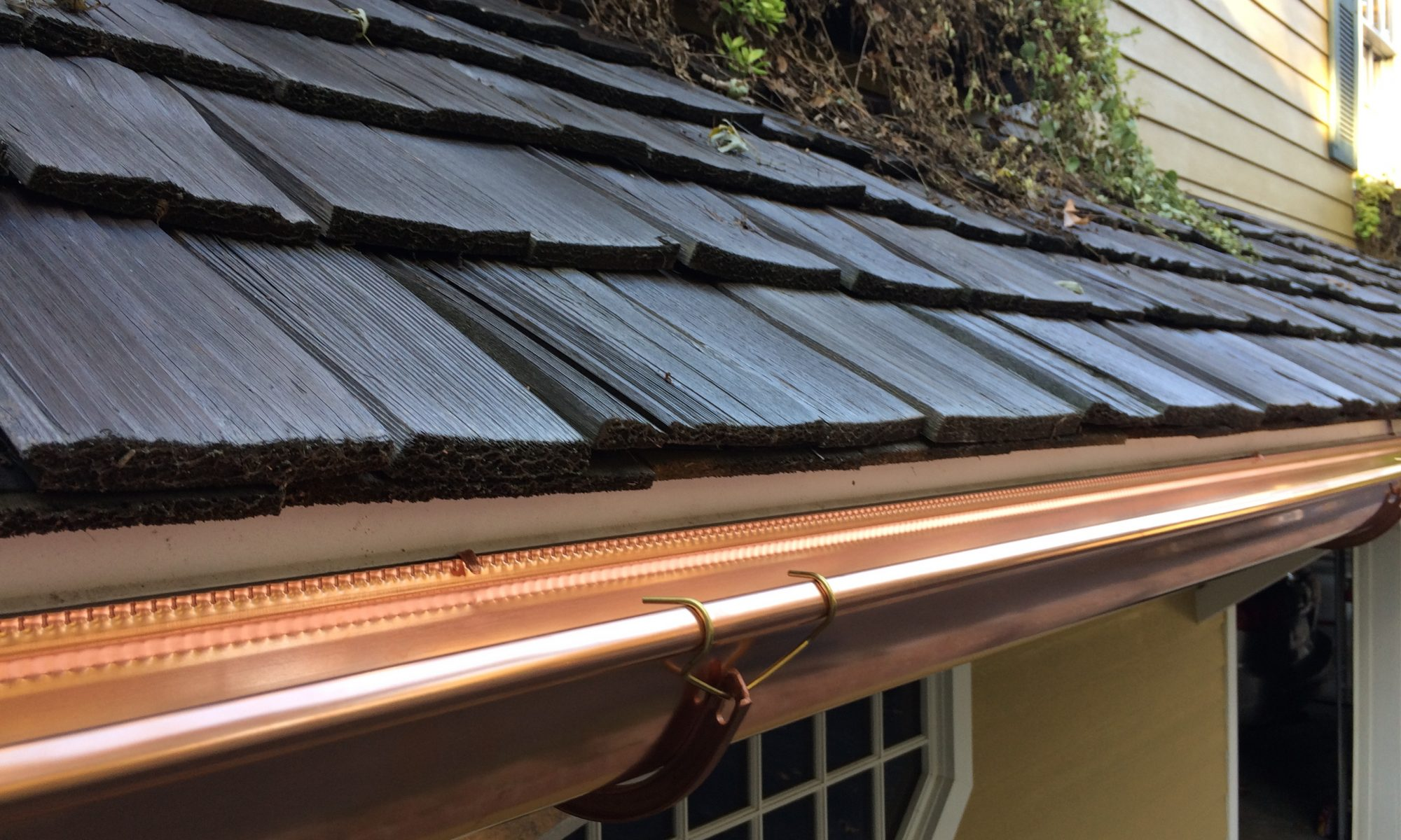 half round copper gutter installed on a wood shake roof