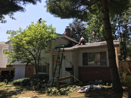 roofers installing shingles on split level house