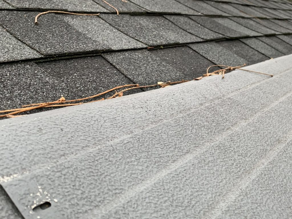 gutter Helmet installed on top of roof shingles with leaf stems lodged between the shingles and gutter guards